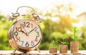 コインの上に置かれた目覚まし時計と植物