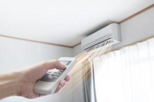 エアコンにリモコンを向け温度調整をしている様子