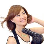 ヘアードライヤーで髪を乾かす女性